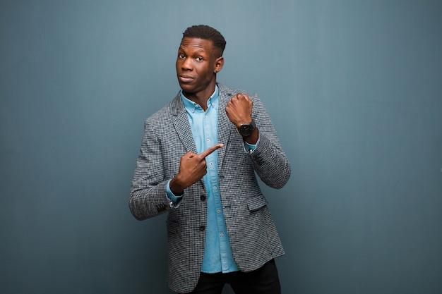 Il giovane uomo di colore afroamericano che sembra impaziente e arrabbiato, indicando l'orologio, chiedendo la puntualità, vuole essere puntuale contro la parete del grunge