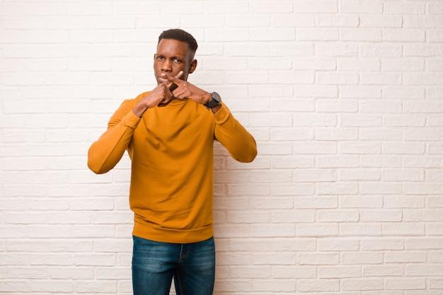 Il giovane uomo di colore afroamericano che sembra serio e scontento con entrambe le dita ha attraversato la parte anteriore nel rifiuto, chiedendo silenzio contro il muro di mattoni