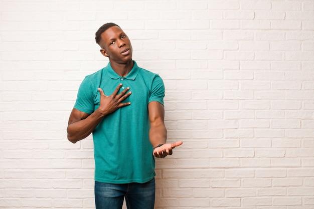 Il giovane uomo di colore afroamericano che si sente felice e innamorato, sorride con una mano vicino al cuore e l'altra allungata davanti sul muro di mattoni