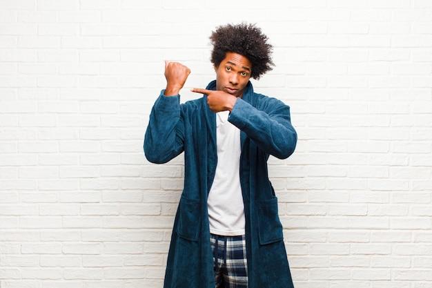 Il giovane uomo di colore che indossa il pigiama con l'abito che sembra impaziente e arrabbiato che punta a guardare chiedendo puntualità vuole essere puntuale contro il muro di mattoni