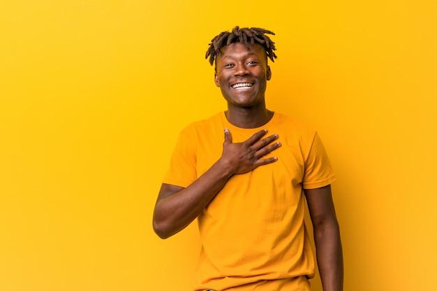 Il giovane uomo di colore che indossa rasta sopra il giallo ride ad alta voce tenendo la mano sul petto.