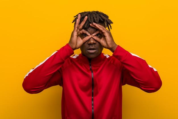 Il giovane uomo di colore di forma fisica che mostra bene firma sopra gli occhi