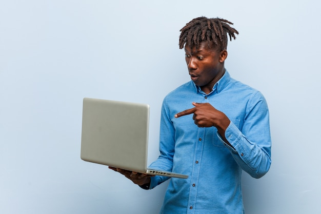 Il giovane uomo di colore di rasta che tiene un computer portatile ha impressionato lo spazio della copia della tenuta sulla palma.