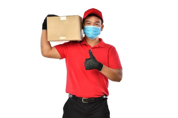 Il giovane uomo di consegna asiatico felice in uniforme rossa, maschera medica, guanti protettivi porta la scatola di cartone nelle mani isolate su bianco. il ragazzo delle consegne dà la spedizione del pacco. consegna sicura