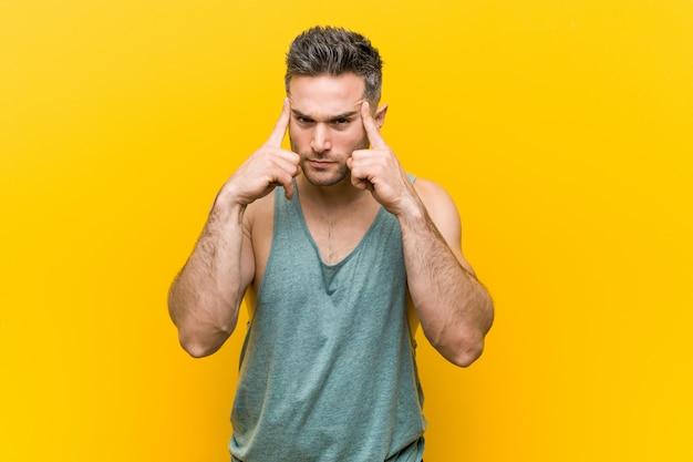 Il giovane uomo di forma fisica contro uno sfondo giallo si è concentrato su un compito, tenendo gli indici che indicano la testa.