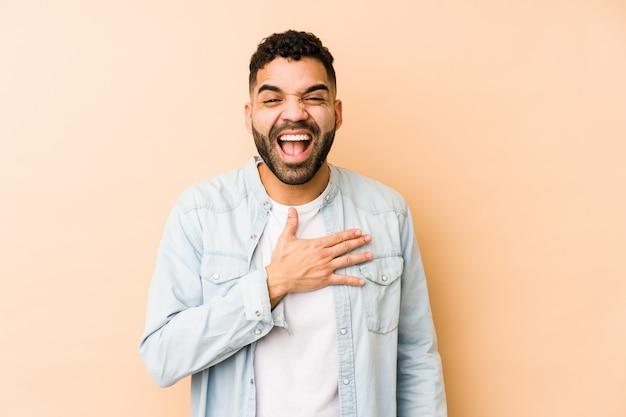 Il giovane uomo di razza mista ride ad alta voce tenendo la mano sul petto