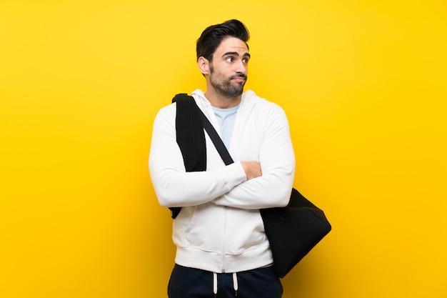 Il giovane uomo di sport sopra la parete gialla isolata che fa i dubbi gesturing mentre solleva le spalle