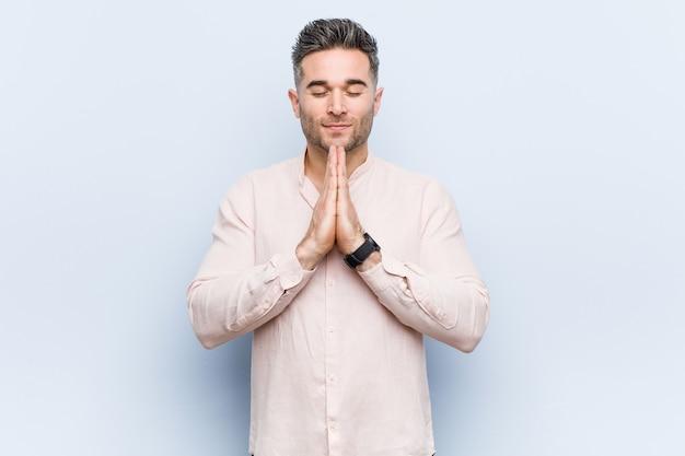 Il giovane uomo freddo bello che si tiene per mano dentro prega vicino alla bocca, si sente sicuro.
