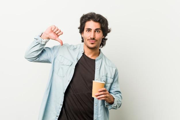 Il giovane uomo freddo che beve un caffè si sente orgoglioso e sicuro di sé, esempio da seguire.