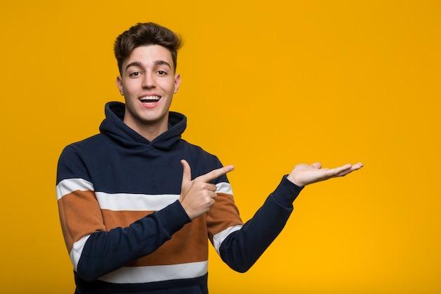 Il giovane uomo freddo che indossa una maglia con cappuccio ha eccitato tenendo uno spazio della copia sul palmo.
