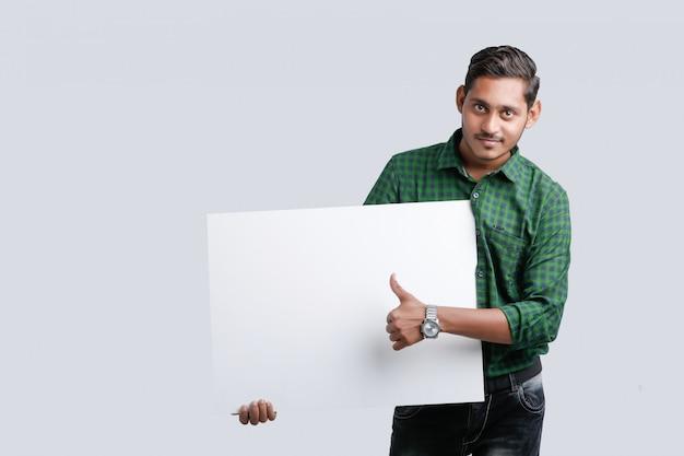 Il giovane uomo indiano che mostra lo spazio in bianco canta il bordo sopra fondo bianco