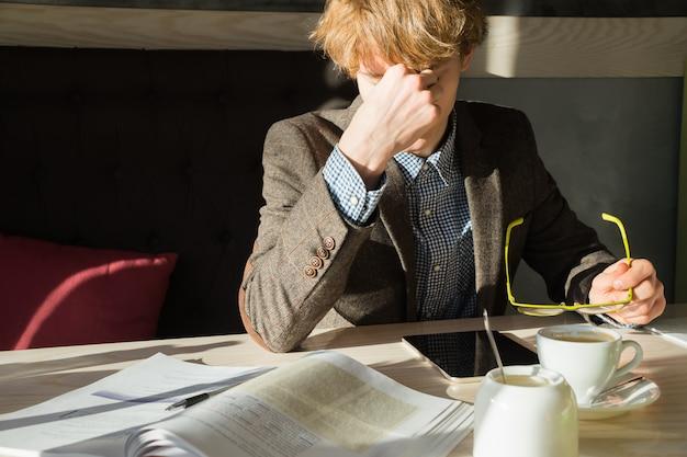 Il giovane uomo intelligente riposa di fare il lavoro o l'assegnazione di progetto dell'università all'ora di pranzo in caffè.