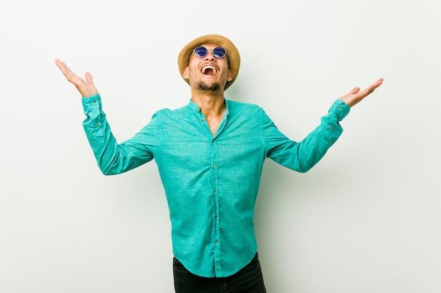 Il giovane uomo ispanico che indossa un'estate copre gridare al cielo, alzando lo sguardo, frustrato.