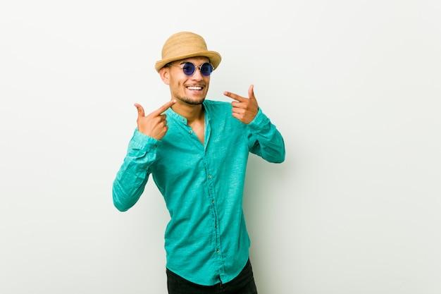 Il giovane uomo ispanico che indossa un'estate copre i sorrisi, indicando le dita alla bocca.