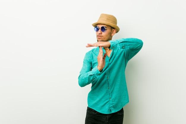 Il giovane uomo ispanico che indossa un'estate copre la mostra del gesto di prespegnimento.
