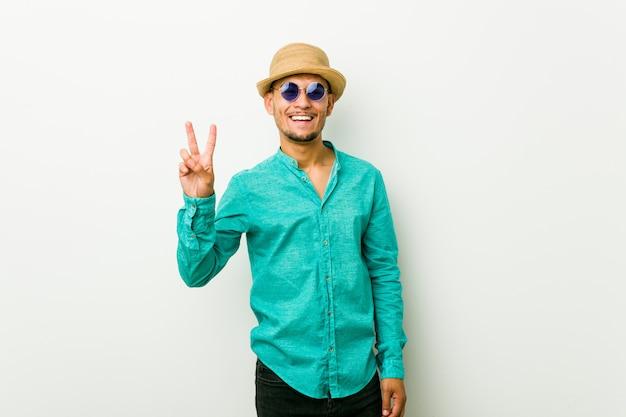 Il giovane uomo ispanico che indossa un'estate copre la mostra del numero due con le dita.