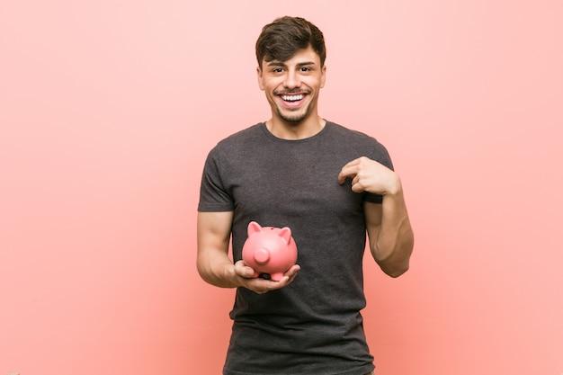 Il giovane uomo ispanico che tiene il porcellino salvadanaio sorpreso indicando se stesso, sorridendo ampiamente.