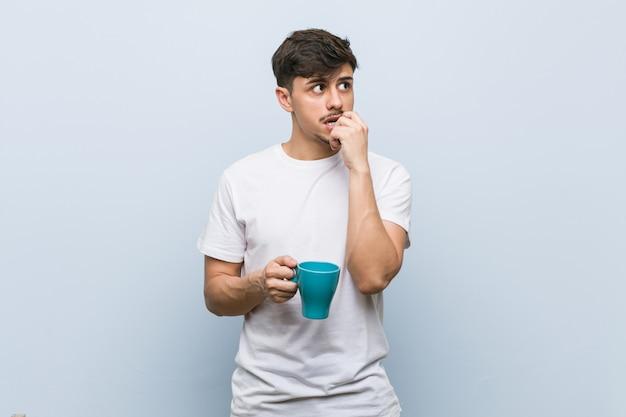 Il giovane uomo ispanico che tiene una tazza si è disteso pensando a qualcosa che esamina uno spazio della copia.