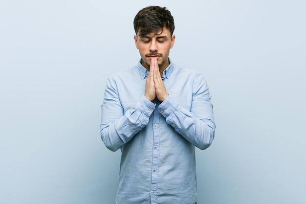 Il giovane uomo ispanico di affari che tiene le mani nella preghiera vicino alla bocca, si sente sicuro.