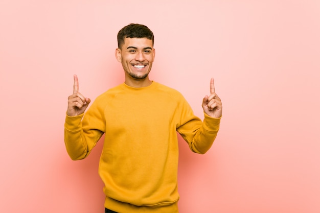 Il giovane uomo ispanico indica con entrambe le dita anteriori in su che mostrano uno spazio.