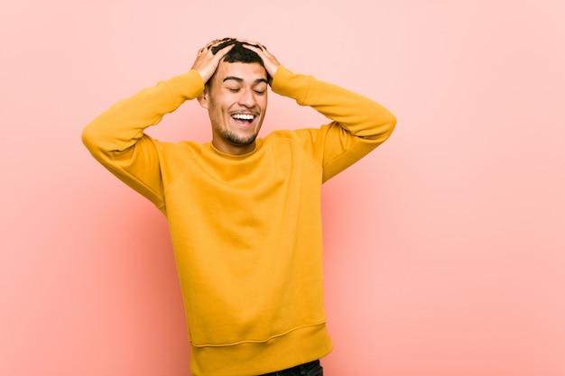 Il giovane uomo ispanico ride con gioia tenendo le mani sulla testa. concetto di felicità.