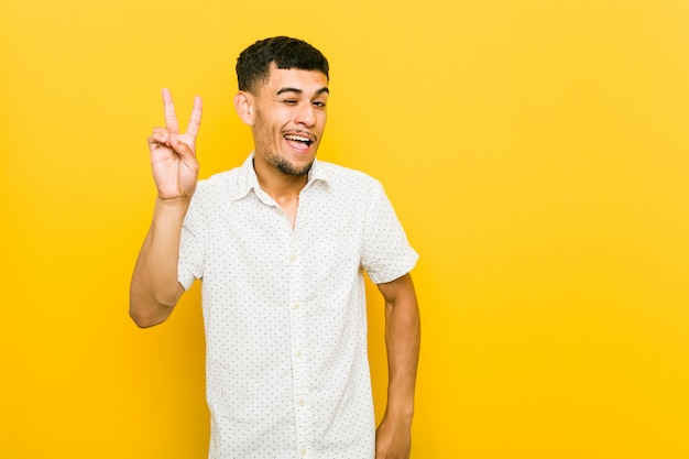 Il giovane uomo ispanico sbatte le palpebre e tiene un gesto giusto con la mano.