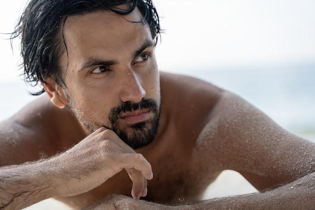 Il giovane uomo latino bello alla moda sexy si trova su una spiaggia tropicale, sabbia su pelle abbronzata, concetto prendente il sole di vacanza.
