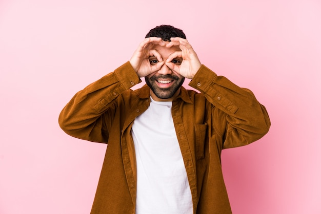 Il giovane uomo latino contro una parete rosa isolata mostrando okay firma sopra gli occhi