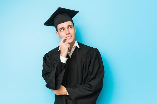 Il giovane uomo laureato caucasico si è disteso pensando a qualcosa che esamina uno spazio della copia.