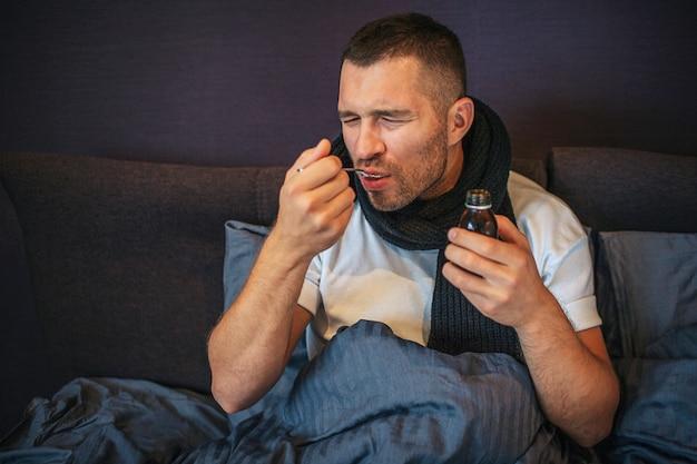 Il giovane uomo malato si siede sul letto con la parte bassa coperta del corpo. mangia sciroppo per la tosse. il giovane tiene gli occhi chiusi. ha una sciarpa intorno al collo. guy ha un trattamento per la guarigione.