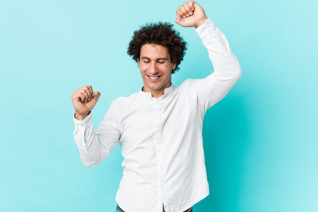 Il giovane uomo maturo riccio che indossa una camicia elegante che celebra un giorno speciale, salta e alza le braccia con energia.