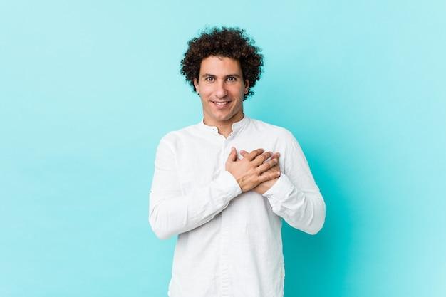Il giovane uomo maturo riccio che indossa una camicia elegante ha un'espressione amichevole, premendo il palmo sul petto. concetto di amore.