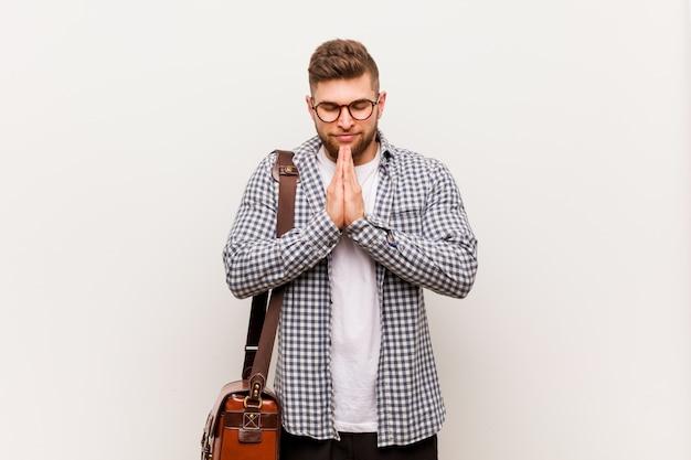 Il giovane uomo moderno di affari che si tiene per mano dentro prega vicino alla bocca
