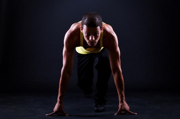 Il giovane uomo muscoloso è pronto per la corsa