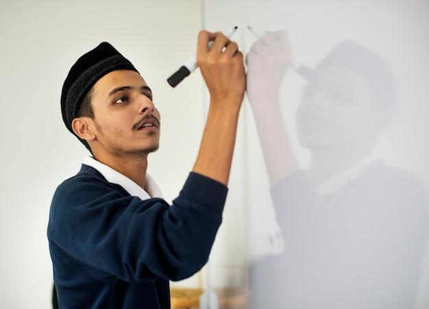 Il giovane uomo musulmano sta scrivendo un bordo bianco