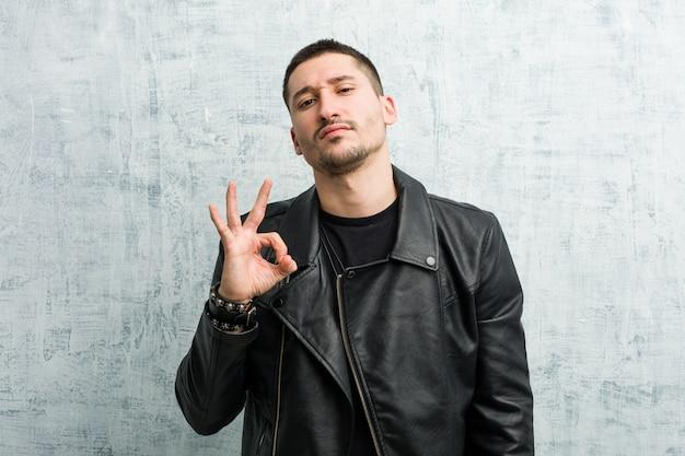 Il giovane uomo rocker strizza l'occhio e tiene un gesto ok con la mano.