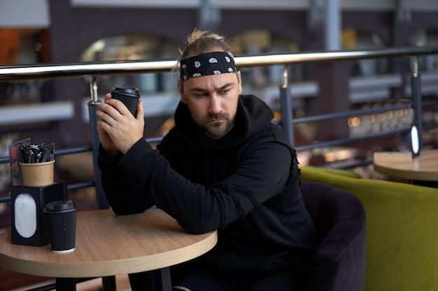 Il giovane uomo solo bello si siede nella tabella del caffè in attesa triste incontro per bere caffè da una tazza di carta.