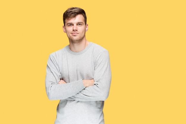 Il giovane uomo sorridente e guardando la telecamera su sfondo giallo
