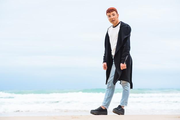 Il giovane uomo stanco alla moda sta posando su una spiaggia