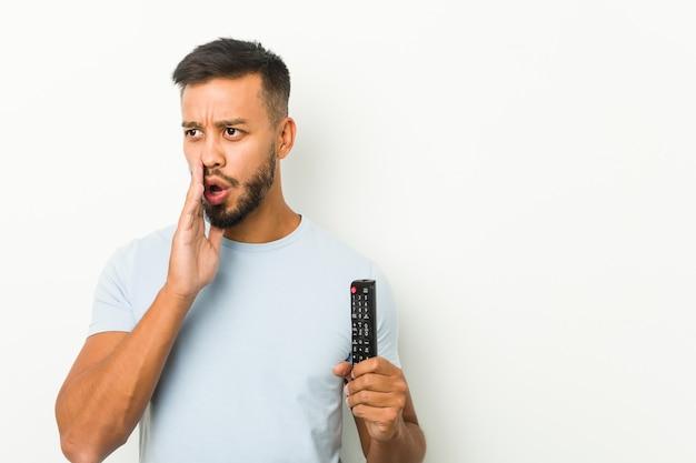 Il giovane uomo sud-asiatico che tiene un controller tv sta dicendo una notizia segreta sulla frenata e sta guardando da parte