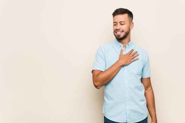 Il giovane uomo sud-asiatico ride ad alta voce tenendo la mano sul petto.