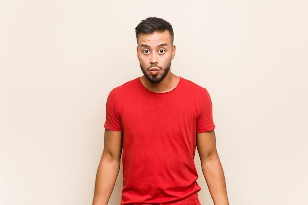 Il giovane uomo sud-asiatico scrolla le spalle le spalle e gli occhi aperti confusi.