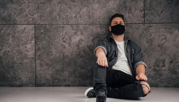 Il giovane uomo triste con la maschera nera nella stanza scura prega per la quarantena del mondo e del coronavirus