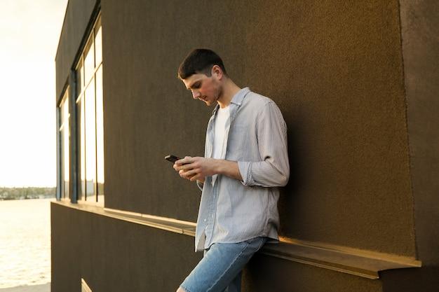 Il giovane usa un telefono all'aperto. scrivere un messaggio