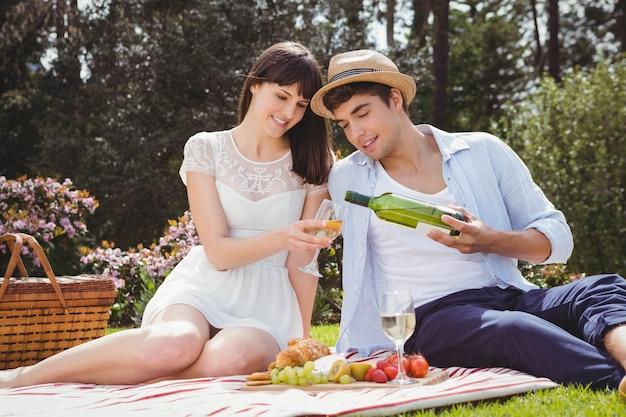 Il giovane versa al vino della donna in un bicchiere durante un picnic
