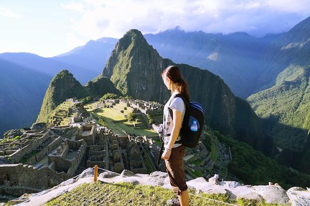 Il giovane viaggiatore asiatico femminile che sta alla scogliera che esamina machu picchu, perù.