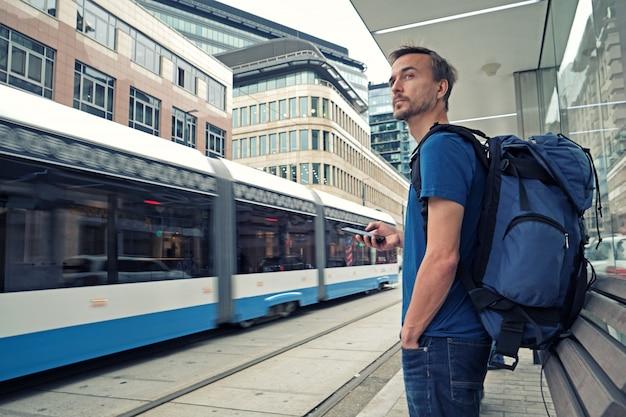 Il giovane viaggiatore maschio con lo zaino e lo smartphone sta sulla fermata del trasporto pubblico e sul tram aspettante nel centro urbano moderno.