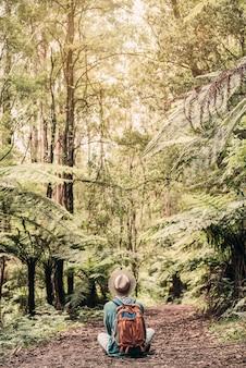 Il giovane viaggiatore perso nella foresta con un cappello si siede e medita sulla terra durante il tramonto