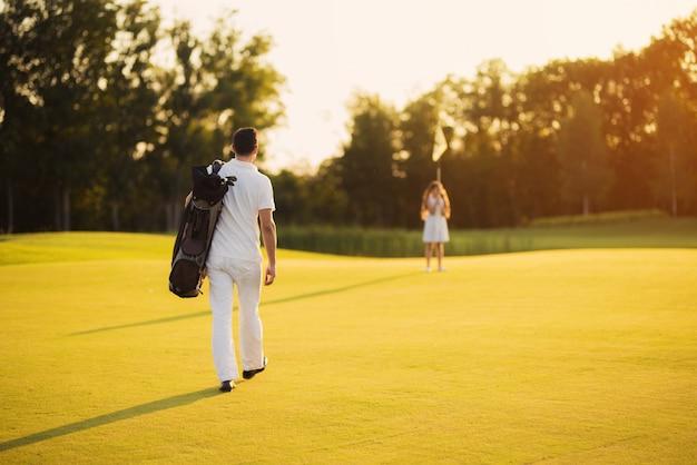 Il golfista cammina per la ricreazione della famiglia del corso.