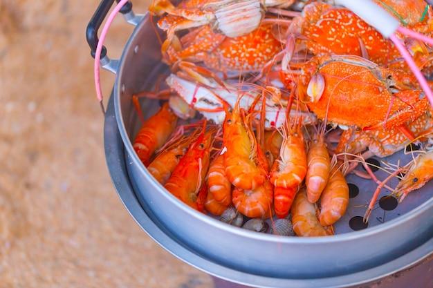 Il granchio ed i gamberetti hanno cotto a vapore la vendita intorno alla spiaggia del mare, pattaya chonburi tailandia.